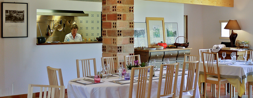 La salle du restaurant Au four et au Moulin et Joëlle Brard dans sa cuisine ouverte