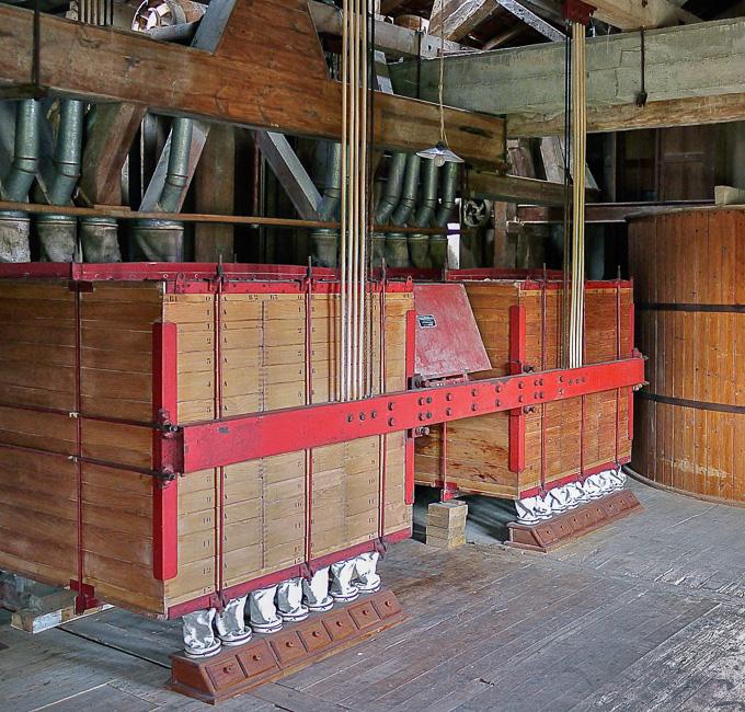 """Le « plansichter », suspendu aux deux poutres en béton par des filins d'acier et des baguettes de rotin, tamisait sur de la soie naturelle, les différents types de farine. A droite, la """"chambre à farine""""."""